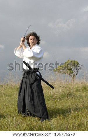 young aikido man with a sword, outdoor
