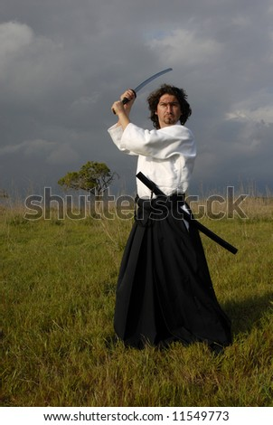 young aikido man with a sword outdoors
