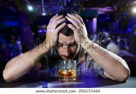 young alcoholic drunk man thoughtful about alcohol addiction drinking indoors at bar of a disco nightclub hands on his head in front of whiskey glass in alcoholism concept
