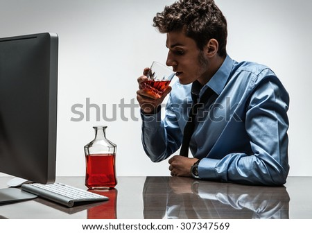 Young alcoholic man drinking whiskey sitting drunk at office with computer / photo of businessman addicted to alcohol at the workplace, depression and crisis concept