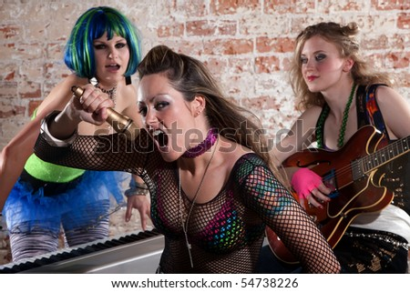 Young all girl punk rock band performs in front of brick wall