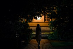 Young alone woman in dress walking on sidewalk through dark park to home in summer black night. Scary moment and gloomy atmosphere. Back view.
