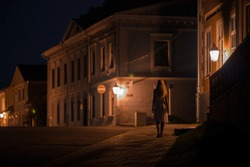 Young alone woman in white dress slowly walking on sidewalk under street lights at old town in dark summer night. Peaceful atmosphere. Spending time alone. City life. Back view.