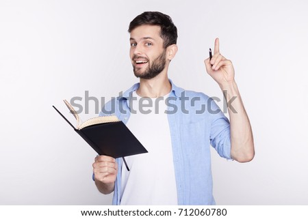 Young amazed Caucasian man with notebook looking at camera with opened mouth showing teeth, pointing his finger at white background with copy space for your advertisement or promotional information. #712060780