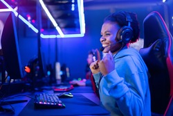 Young American African smile woman professional gamer win in online video game with headphones, neon background.
