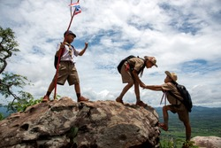 Young American Boy Scouts Help pull up from the cliff.