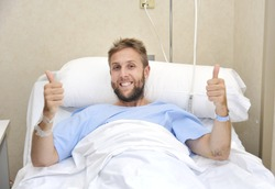 young American man lying in bed at hospital room sick or ill but giving thumbs up smiling happy and positive fighting against disease with energy