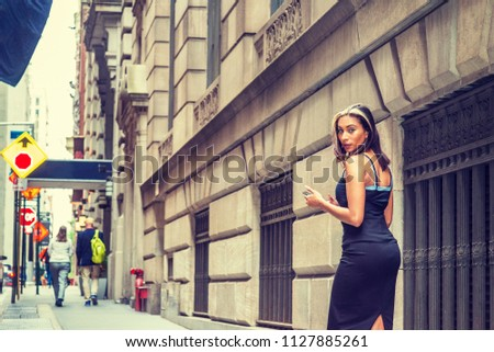 Young American Woman with black hair, dyed front top little blonde, wearing black sleeveless open back dress, walking on street by vintage wall with windows in New York, texting, turning back, looking #1127885261