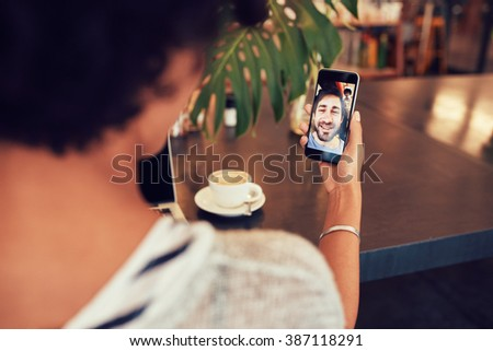 Young an and woman talking to each other through a video call on a smartphone. Young woman having a videochat with man on mobile phone. Woman sitting at a coffee shop. Stock photo ©
