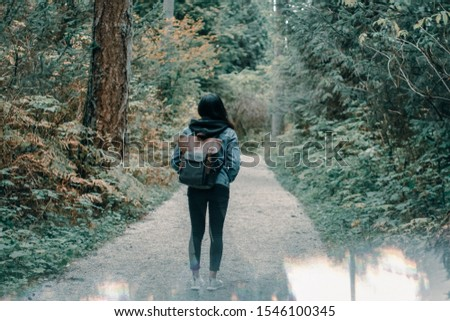 Young and adventurous looking person along a hiking trail in the forest. Travel and adventure.