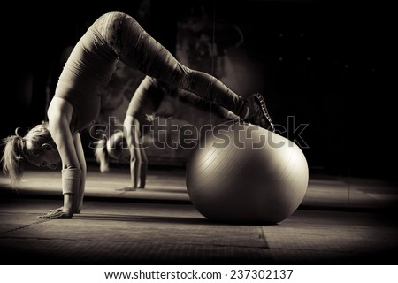 Young and athletic girl using fitness ball in a gym. Fitness ball at gym workout fitness and pilates exercise.Young woman doing some pilates exercises with a ball