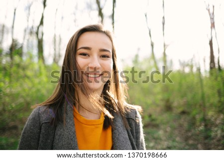 Young and attracive woman standing and laughing in the woods. Lifestyle,health and enviromental protection concept. Vintage analog film look.