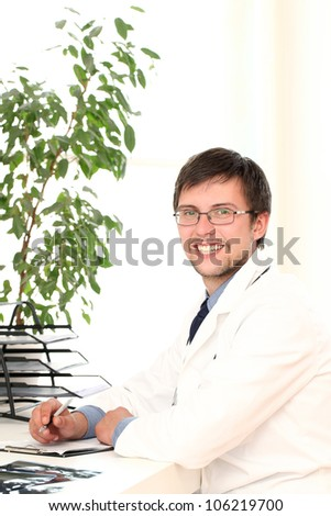 Young  and attractive doctor working in his office