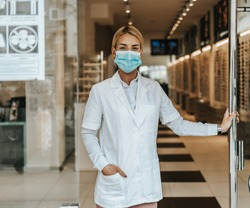Young and attractive female optometrist with face protective mask standing at open optical store doors and looking outside. She is confident and serious. Covid-19 open for business concept.