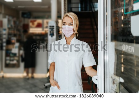 Young and attractive female pharmacist with face protective mask standing at open drugstore doors and looking outside. She is confident and serious. Covid-19 open for business concept.