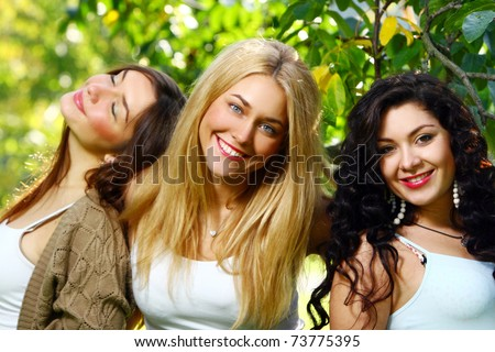 Young and attractive girlfriends posing and have fun in park