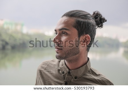 Young and attractive guy with a male hair bun on top of his head