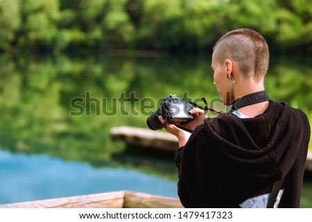 Young and attractive photograph with a shaved head working in a natural environment, taking photographs of the beautiful landscape.