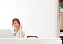 Young and attractive professional businesswoman sitting at her work desk against a white wall and using a laptop computer and a telephone to make a phone call in her office, interior.