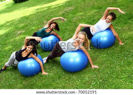 Young and attractive womans doing fitness exercises in park