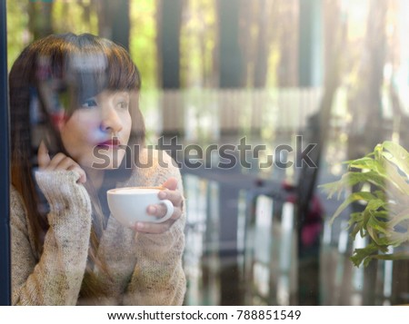 Young and beautiful Asian girl in white dress with drinking hot coffee from white coffee cup looking forward in glasses window at coffee shop