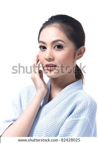 Young and beautiful asian woman touching her face