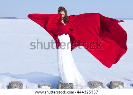 Young and beautiful bride with the red fabric playing with wind in winter background. - Shutterstock ID 444325357