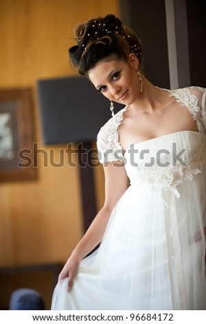 young and beautiful brunette bride in long dress smiling