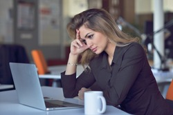 Young and beautiful businesswoman tired from work in the office.Woman holding her head.