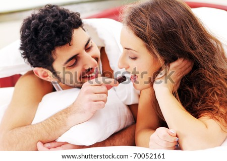 Young and beautiful couple having breakfast in bed