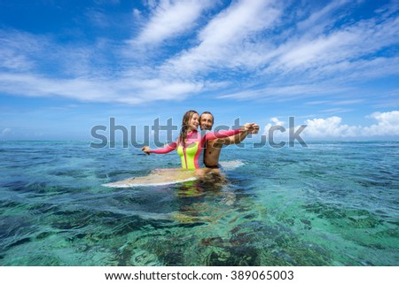 Young and beautiful couple of lovers sitting on a surfboard in the open ocean on a background of clouds. Mauritius island, Indian Ocean