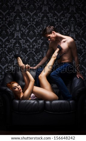 Young and beautiful couple on the leather sofa