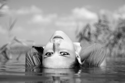 Young and beautiful savage girl in the river. Photo in noisy black and white style.