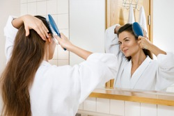 Young and beautiful woman combing her hair with a hairbrush