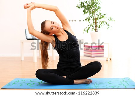 young and beautiful woman do yoga exercises at home on