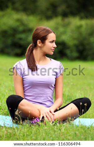 Young and beautiful woman doing her yoga workout on the park`s lawn