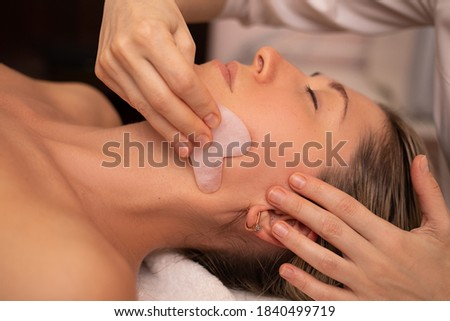 Young and beautiful woman during Chinese traditional massage - Gua Sha with stone. Close-up photo. Beauty treatment in SPA salon. Anti-aging skin care Foto stock ©
