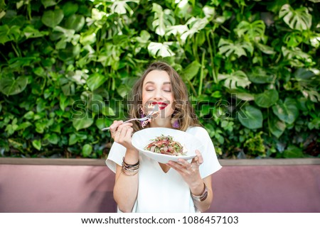 Young and beautiful woman enjoying heathy salad sitting at the vegetarian restaurant with living wall of green plants indoors. Healthy food concept