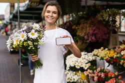 Young and beautiful woman florist holding a bouquet of wildflowers and smartphone with a blank display in her little flower shop