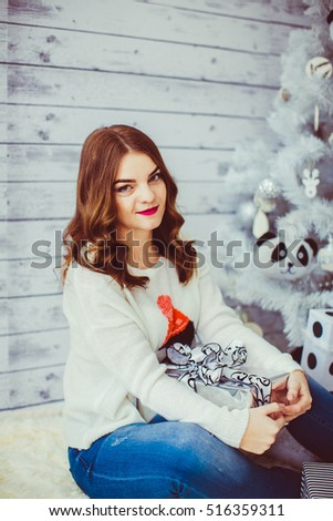 young and beautiful woman holding a box and sitting near the Christmas tree #516359311