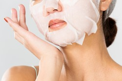 Young and beautiful woman with a clean mask on her face.
