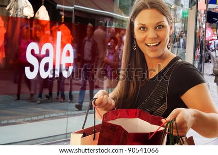 young and beautiful woman with shopping bags in front of shopping window