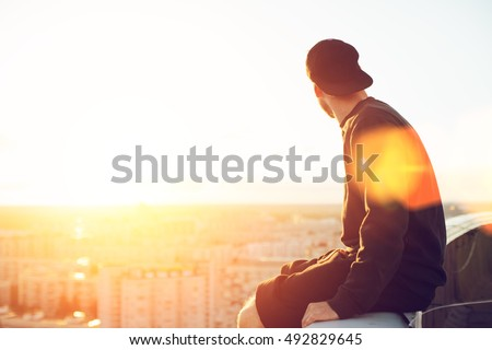 Young and brave man sitting on the edge of the roof and looking far away at the city, lens flares