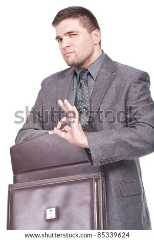 young and businessman holding a briefcase and making ok sign - stock photo