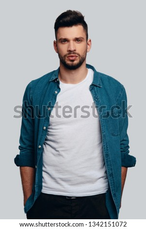 Young and charming. Charming young man looking at camera and keeping hands in pockets while standing against grey background
