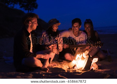 young and cheerful friends sitting on beach and fry sasuages or weenies in bonfire One man is playing guitar. Music on Wild beach. Happy couple relationships. Stock photo ©