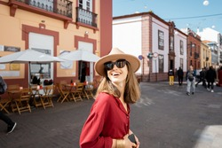 Young and cheerful woman walking on the street with beautiful old buildings at the old town of La Laguna city, traveling on Tenerife island, Spain