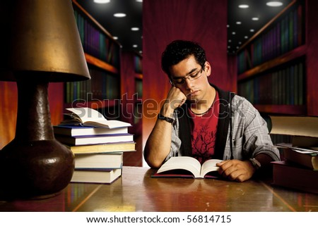 young and concentrated student reads a book