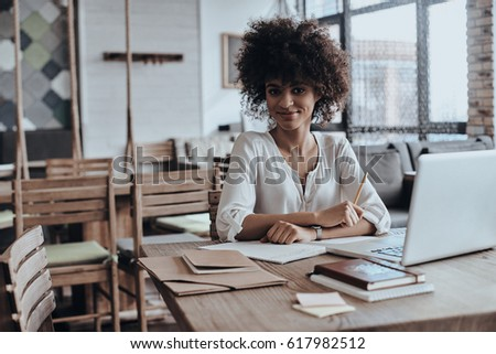 Young and confident. Beautiful young African woman in smart casual wear smiling and looking at camera while sitting in restaurant - Shutterstock ID 617982512