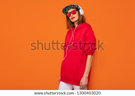 young and cool, hipster girl with colored hat and headphones standing on a orange background